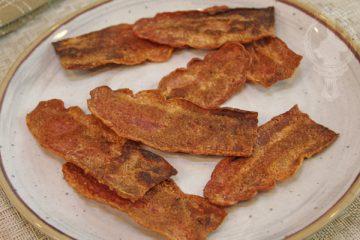 Plate of Crispy Turkey Bacon broken in halves.