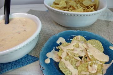 Showing bowl of queso dip, bowl of tortilla chips and a plate with queso drizzled over the chips