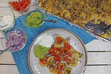 Showing the sheetpan with the base ingredients for the beef nachos and the plate with toppings on the nachos.