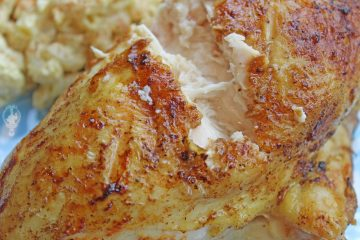 Close up of a grilled chicken breast with a chunk cut out to show the meat.