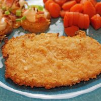 A dinner plate with a pork chop, carrots and potato slices.