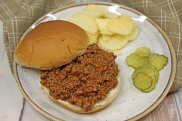 Overhead view of sloppy joes on a bun with chips and pickles on a plate.
