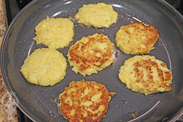 Squash fritters in the frying pan. Some have been flipped.