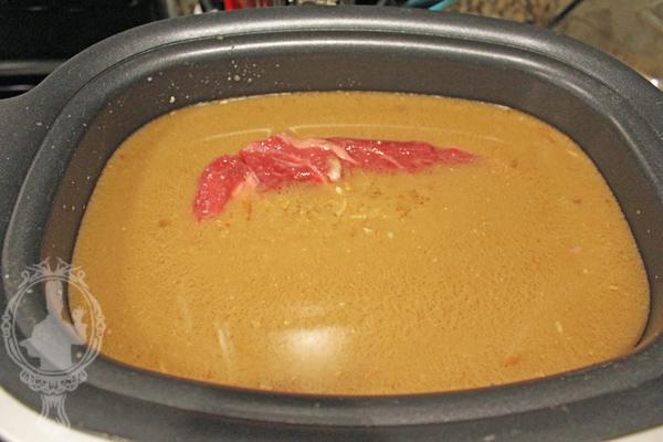 Raw roast beef in broth mixture.