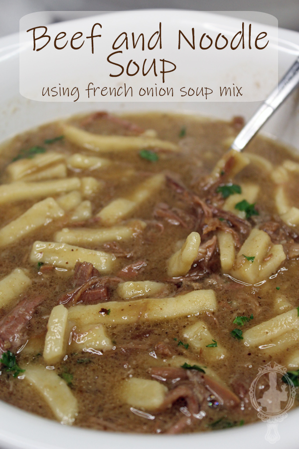 Close up of a bowl of Beef and Noodle Soup with a spoon ready to scoop up a bite.