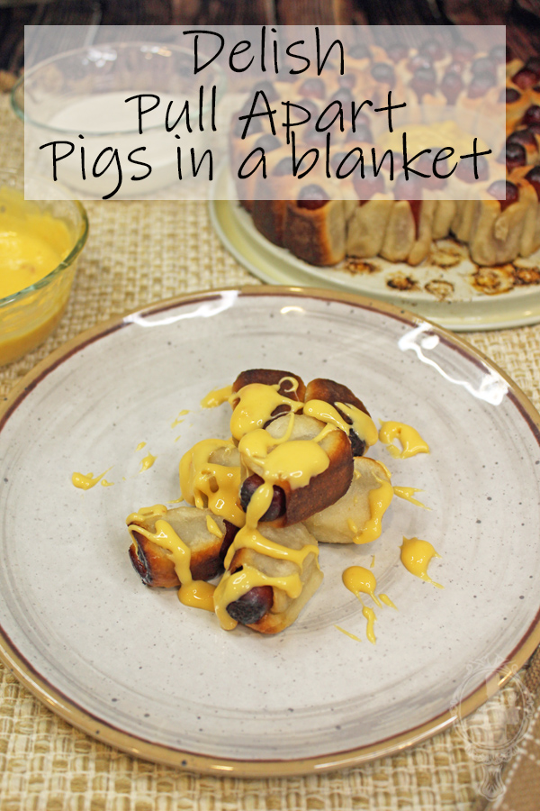 Some pigs in a blanket with cheese dip drizzled over them.