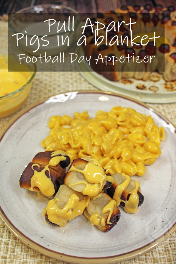 Pigs in a blanket with cheese drizzled over next to a serving of mac and cheese.