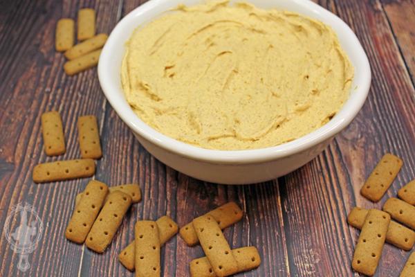 Pumpkin pie dip in a serving bowl with graham cracker sticks scattered around it.