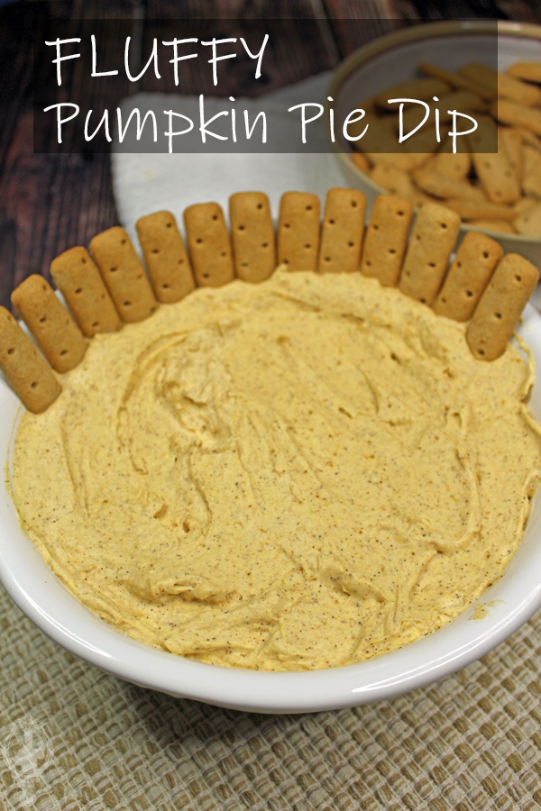 Serving bowl of pumpkin pie dip with graham cracker sticks inserted in the dip.
