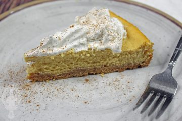 A slice of pumpkin cheesecake on a plate with a fork on the side.