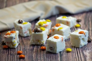 Angle view of Reeses Pieces White Chocolate Fudge with Reeses Pieces candy scattered around.