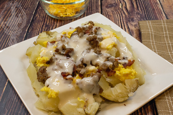 Baked potato with scrambled eggs, sausage, bacon, and country gravy on top.