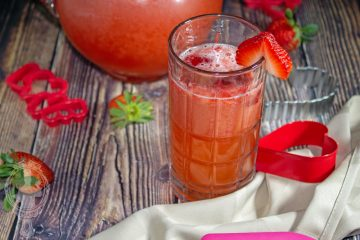 View of a pitcher of Strawberry Spritezer with a tall glass in front of it.