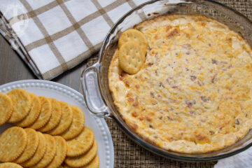 Overhead view of hot cream cheese dip with crackers to the side.